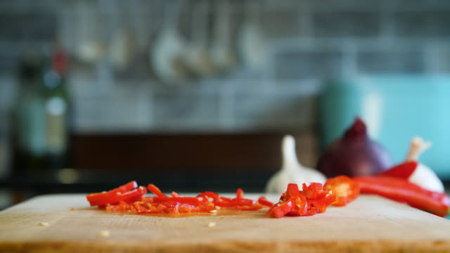 a red chili pepper is chopped into fine slices with a knife - preparing food stock videos & royalty-free footage