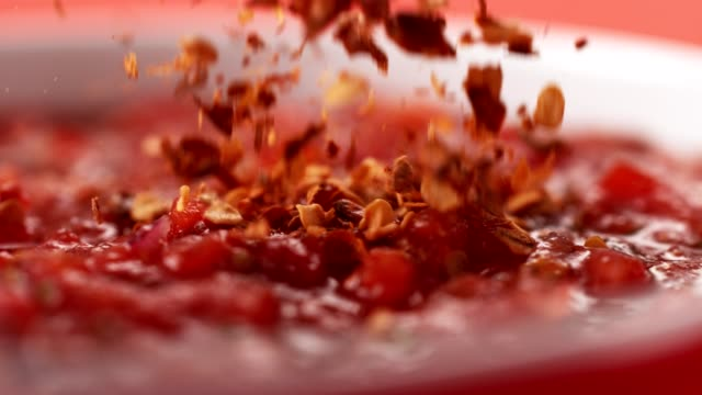 red chili pepper spice falling into hot mexican sauce. - tomato stock videos & royalty-free footage