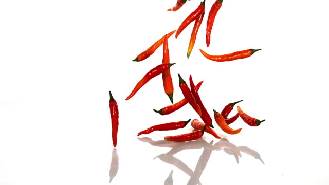 red chili peppers, capsicum annuum falling against with background, slow motion - peperone video stock e b–roll