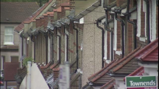red chimneys top row houses in a london neighborhood. - villetta a schiera casa video stock e b–roll