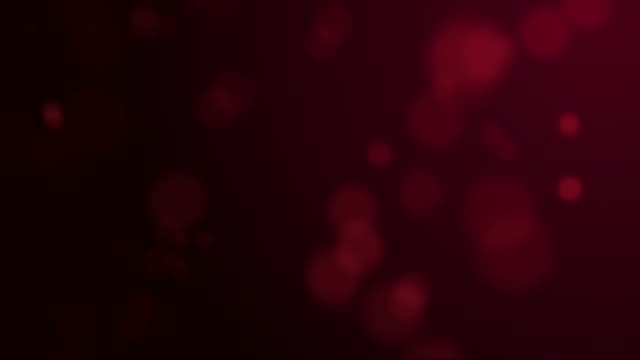 red colored bokeh effect on black background - christmas stock videos & royalty-free footage