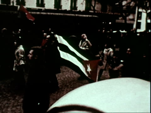 red communist flag being waved in paris france during student demonstration against the war in vietnam tame but large crowd in streets some carrying... - 1969年点の映像素材/bロール