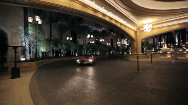 a red convertible enters the palazzo hotel in las vegas. - オープンカー点の映像素材/bロール