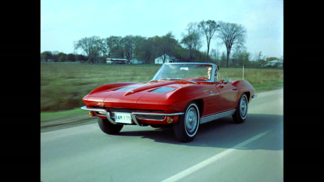 red corvette convertible stingray driving, front view - auto convertibile video stock e b–roll