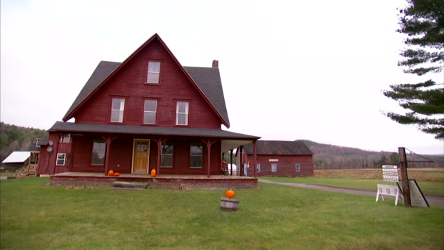 Red countryside farm house on field barn behind house BG Country rural NH