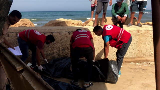 red crescent aid agency zip up body bag of migrant washed up on libyan beach who died after attempting crossing from libya to europe across the... - hopelessness stock videos & royalty-free footage