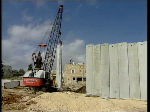 vídeos de stock e filmes b-roll de red cross condemns security wall itv crane lifting concrete block into position as part of the security barrier being built to separate israeli and... - divisa