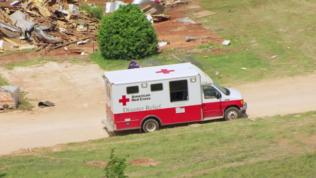 ms aerial red cross disaster relief truck sitting by destruction of building in tornado path / woodward, oklahoma, united states - 緊急援助点の映像素材/bロール