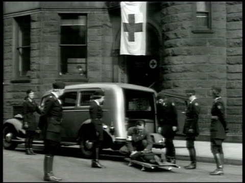 red cross motor corps women watching man tending to patient on stretcher small group of volunteers in red cross uniforms lifting stretcher into... - red cross stock videos & royalty-free footage