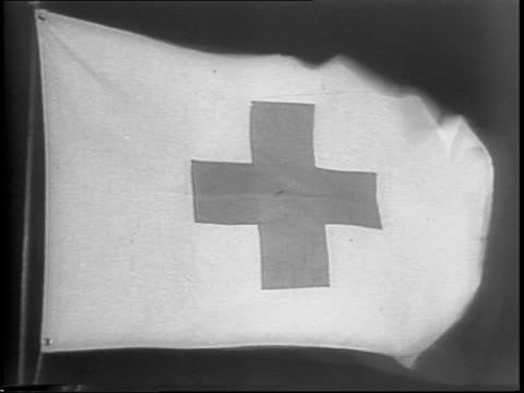 red cross nurse looks at the pin on her uniform / soldiers run across a smoky battlefield / tanks driving through gunfire and smoke / red cross medic... - first aid kit stock videos & royalty-free footage