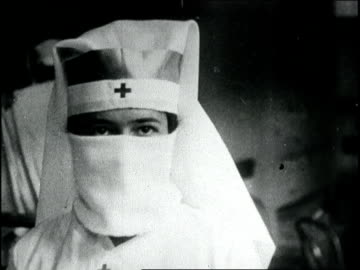 stockvideo's en b-roll-footage met red cross nurses make gauze masks for influenza patients. nurse demonstrates wearing mask. spanish influenza epidemic on january 01, 1918 in boston,... - epidemie