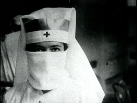 red cross nurses make gauze masks for influenza patients. nurse demonstrates wearing mask. spanish influenza epidemic on january 01, 1918 in boston,... - epidemia video stock e b–roll