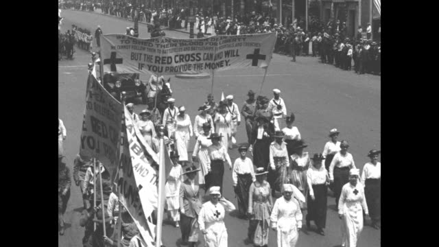 red cross nurses marching down street flanked by lines of soldiers and sailors marching along with them crowd watching / red cross nurses marching... - parade stock videos & royalty-free footage