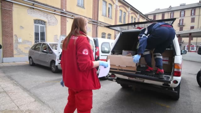red cross volunteers load boxes of food to deliver as a donation to families in need during the current coronavirus epidemic at the turin red cross... - red cross stock videos & royalty-free footage