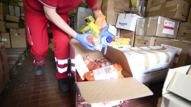 red cross volunteers prepare the boxes with food as a donation for families in need during the current coronavirus epidemic at the turin red cross... - red cross stock videos & royalty-free footage