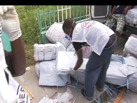 vídeos de stock e filmes b-roll de red cross workers begin to organise aid supplies before distributing them to victims following devastating earthquake haiti; 17 january 2010 - hispaniola