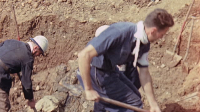 Red Cross workers digging and removing corpses from a mass grave French flag blowing over the exhumation site and officials watching from the grave's...
