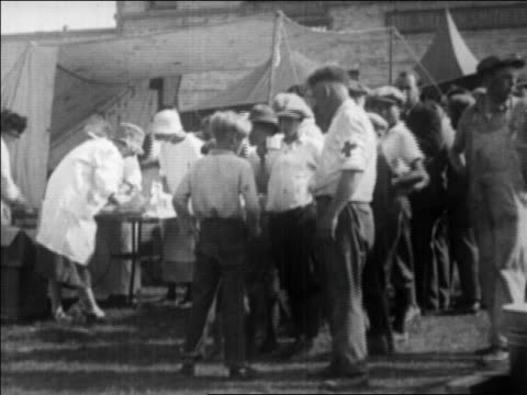 red cross workers feeding people after earthquake / santa barbara, ca / newsreel - anno 1925 video stock e b–roll