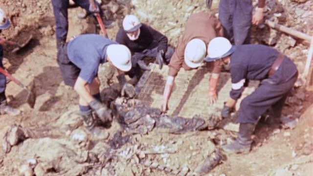 vidéos et rushes de red cross workers removing decayed entangled corpses from a mass grave / lyons france - creuser