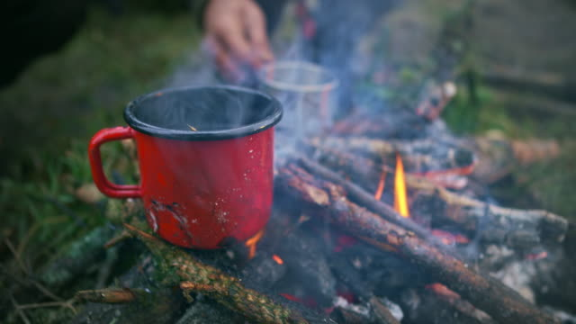 red cup set on the twigs of the camp fire - eco tourism stock videos & royalty-free footage