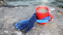 Red cup with hot coffee tea and steam, tied with blue knitted scarf