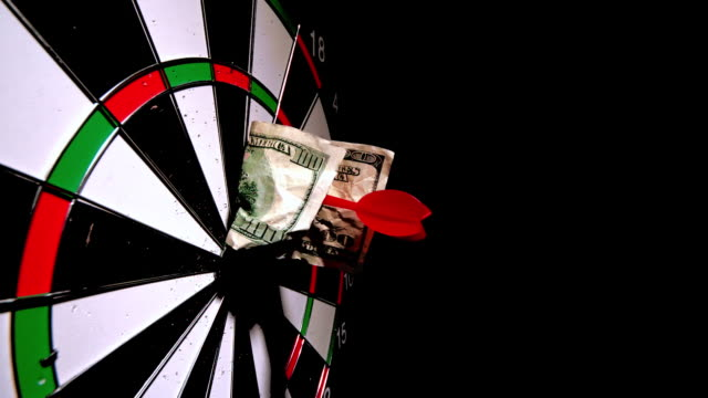 red dart with a dollar note hitting board - dart board stock videos & royalty-free footage