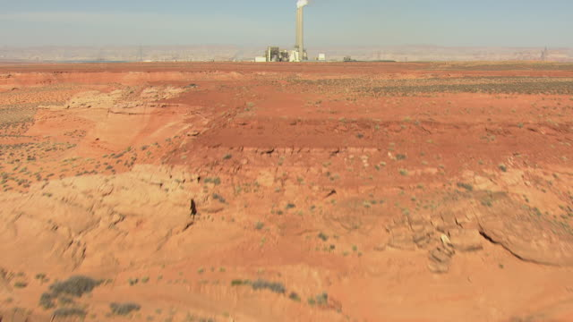 ws aerial red desert to reveal navajo generating station / arizona, united states - 工場の煙突点の映像素材/bロール