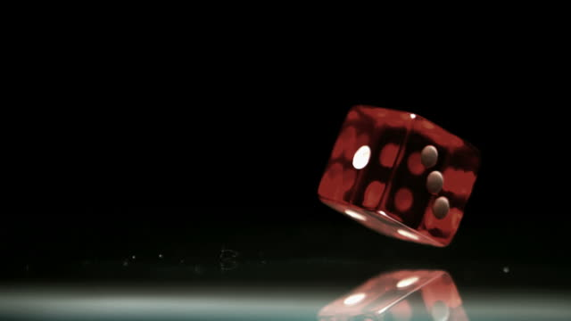 Red dice falling and bouncing close up