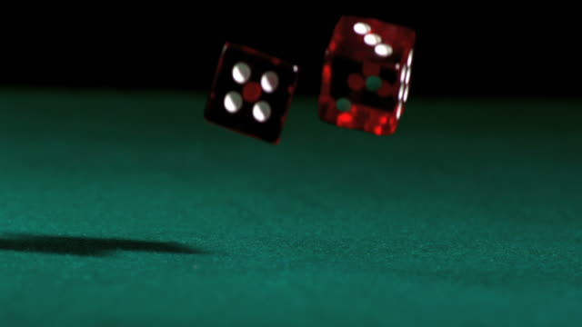 Red dice falling and bouncing on green table