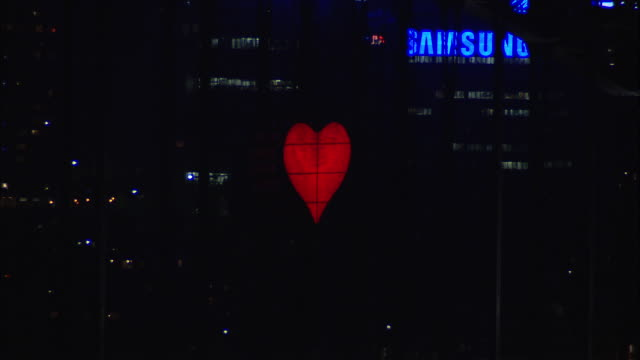 a red digital heart projection pulses on a sydney building during a new year's eve celebration. - heart shape stock videos & royalty-free footage