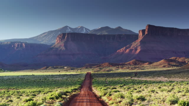 red dirt road through castle valley, utah - aerial shot - moab utah stock videos and b-roll footage