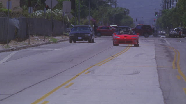 A red Dodge Viper convertible spins to a fast stop then drives in reverse.