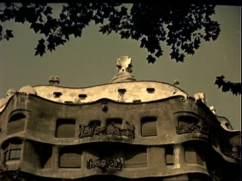 red double decker bus driving along street in barcelona passing casa mila aka milo house designed by antoni gaudi / steam engine locomotive train... - trolley bus stock videos & royalty-free footage