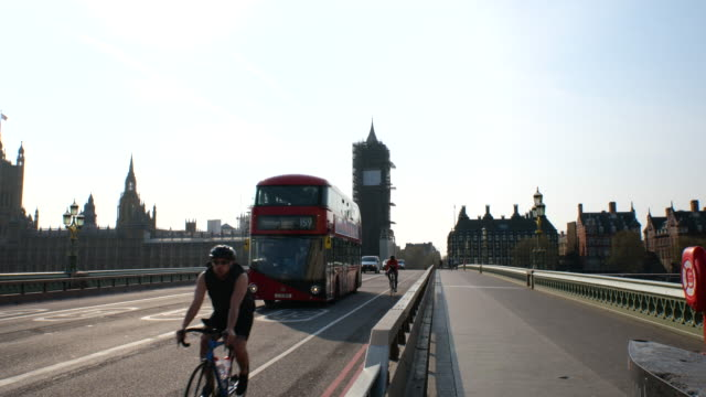 red double decker bus goes over westminster bridge with cyclists and big ben under renovation during lockdown for coronavirus pandemic in london,... - big ben stock videos & royalty-free footage