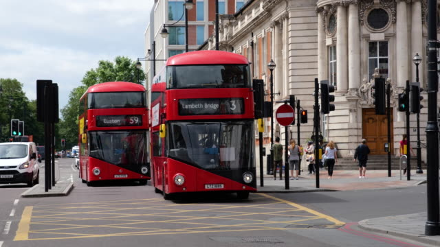 red double decker buses and car traffic passing lambeth town hall on brixton road during lockdown for coronavirus pandemic in london, england, uk, on... - lambeth stock videos & royalty-free footage