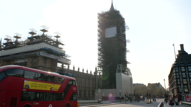 red double decker buses go over empty westminster bridge overlooking big ben under renovation during lockdown for coronavirus pandemic in london,... - red stock videos & royalty-free footage