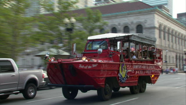 WS TS Red Duck Tour boat driving up Boylston Street, Boston Public Library in background / Boston, Massachusetts, USA