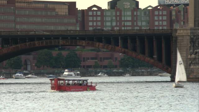 ZO WS PAN Red Duck Tours boat speeding down Charles River towards Longfellow Bridge, downtown buildings in background / Boston, Massachusetts, USA