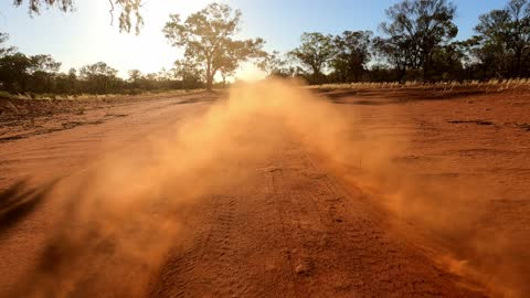 red dust clouds behind moving car on dirt road, outback australia, rear of car view - extreme terrain stock videos & royalty-free footage