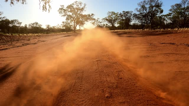 vidéos et rushes de red dust clouds behind moving car on dirt road, outback australia, rear of car view - paysage extrême