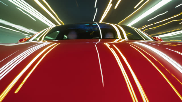 Red electric powered car drives on city highway while night - lots of tunnels and streaking lights.