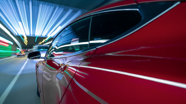 red electric powered car drives on city highway while night - lots of tunnels and streaking lights. - wissenschaft und technik stock-videos und b-roll-filmmaterial