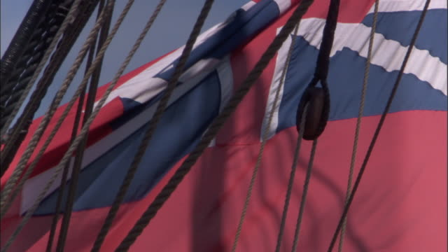 Red ensign (1707-1801) flutters on stern of replica of HMS Endeavour.