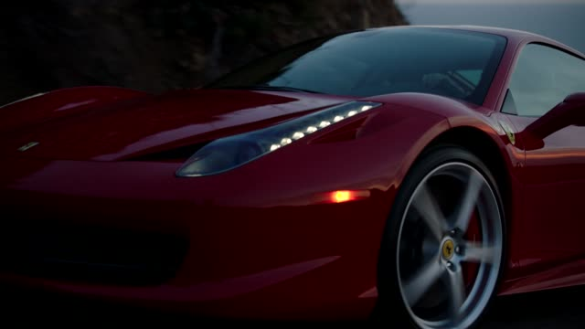 Red Ferrari driving down Malibu Canyon during Sunset overlooking Pacific Ocean