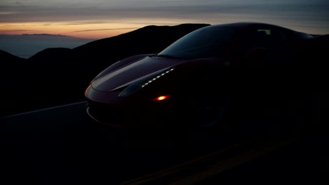 vídeos y material grabado en eventos de stock de red ferrari driving down malibu canyon during sunset overlooking pacific ocean - ferrari