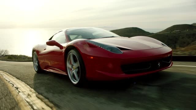 red ferrari driving up malibu canyon overlooking pacific ocean - 汽車 個影片檔及 b 捲影像