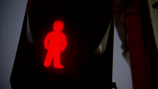 A red figure glows on a crosswalk sign.