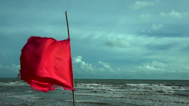 red flag the sea with clouds and sunlight,danger warning - flag blowing in the wind stock videos & royalty-free footage