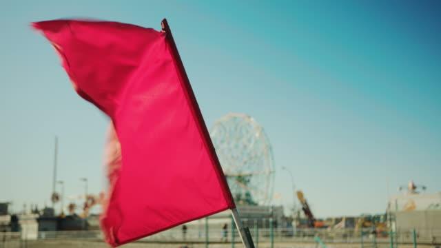 bandiera rossa sventolare al vento, ruota panoramica sullo sfondo - in rovina video stock e b–roll