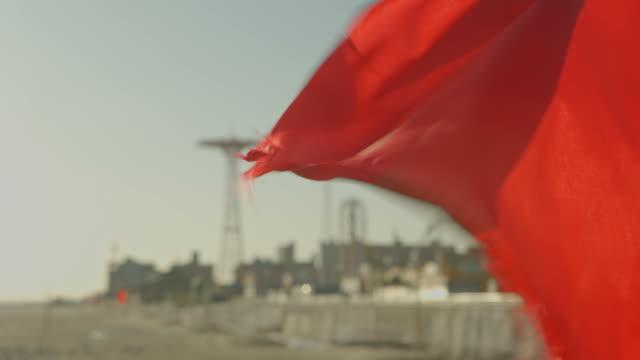 bandiera rossa sventolare al vento in background parco di divertimento - in rovina video stock e b–roll